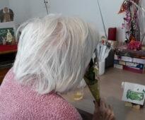 Eine Bewohnerin erfreut sich an dem Duft der Maiglöckchen